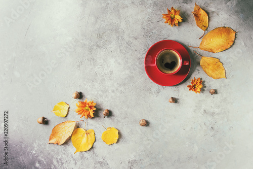 Fototapeta Red cup of black coffee decorated by yellow autumn leaves, aster flowers and acorns over grey texture background. Flat lay, space. Seasonal background. Heart shape on foam