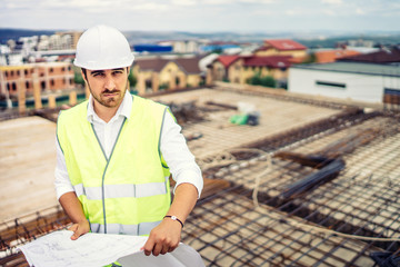engineer on construction site, portrait of man wearing hardhat and safety equipment on building site