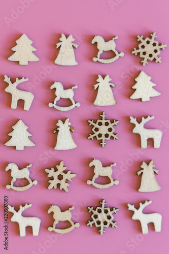 Christmas pink background. Wooden Christmas figurines of a Christmas tree, a bell, a deer and snowflakes on a pink background. vertical photo - 220507880