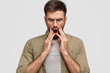 Emotional Man  Horrified Stupefied Expression Holds Hands Near Opened Mouth Stares At Floor  Frightened Look Has Dark Stubble Dressed In Stylish Shirt Poses Indoor Against  Wall Sticker
