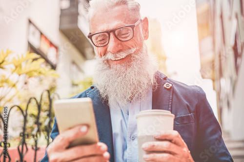 Happy senior man using smartphone app outdoor while drinking take away coffee - 220535405