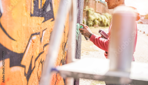 Tattooed graffiti writer painting with color spray his picture on the wall - Contemporary artist at work - 220535869