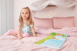 Cute little girl reading bedtime story at home - 220536668