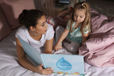 Mother reading bedtime story to her little daughter at home - 220536691