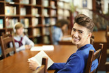 Student with book studying in library - 220537069