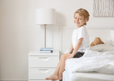 Cute little boy sitting on bed at home - 220537072
