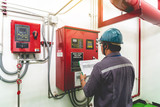 Engineer checking industrial generator fire control system - 220540009