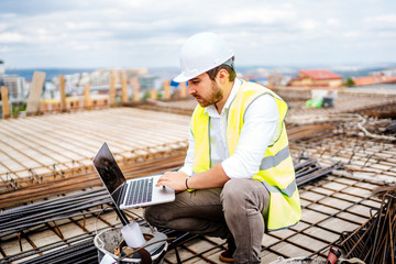 Construction engineer, architect planning with laptop, using technology at construction site