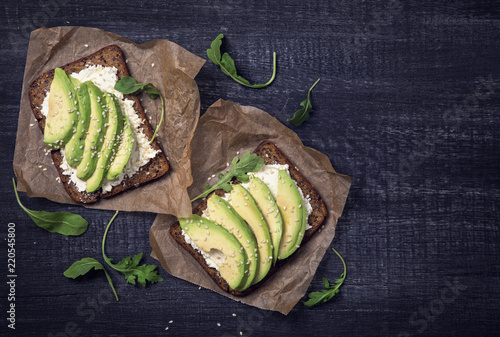 Sandwiches with rye bread and fresh sliced avocado - 220545800