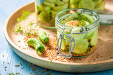 Natural and healthy canned cucumber on blue table - 220553239