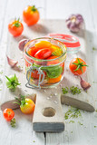 Natural and healthy pickled red tomatoes in the jar - 220553282