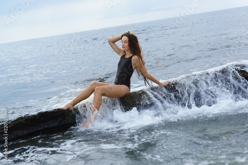 72ced3620c8e A beautiful slender long-haired girl in a black swimsuit sits on a stone on