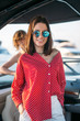 Leinwanddruck Bild - Outdoor portrait of cute brunette lady, fashionably dressed in red blouse, wearing trendy sunglasses, smiling at camera, in anticipation of intresting sea trip on speed boat