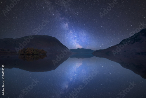 Poster Vibrant Milky Way composite image over landscape of Crummock Water in Lake District England