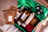 Beauty box with bottles of natural cosmetics, wrapped in green paper. Blogger hair and body care routine, salon treatments. Minimalism - 220575641