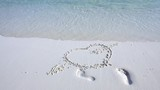 Handwriting shape of heart with hand palm prints drawn on sand at maldivian beach - 220583204