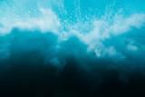 Wave in underwater. Wave crashing on beach, clouds of water - 220587407