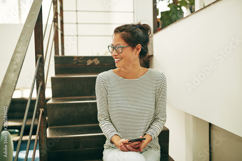 Laughing young Asian businesswoman sitting on office stairs read