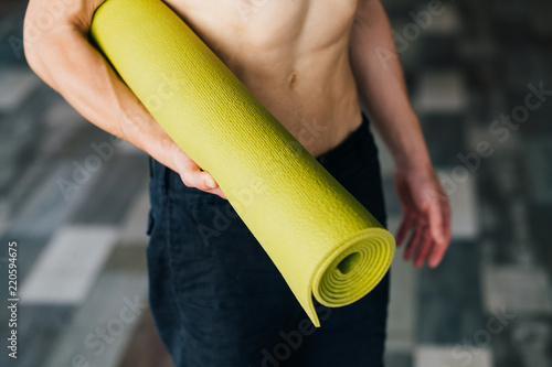 Wall mural sport equipment. handy and useful yoga mat for the best training performance. unrecognizable man holding a bright green mat. health and fitness concept.