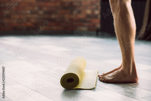 Wall mural sport fitness and gym training. taking care of your body health. male legs standing in front of a yoga mat preparing to exercise.
