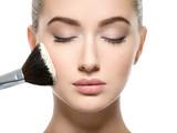 Girl applies  powder  on the face using makeup brush. - 220597288