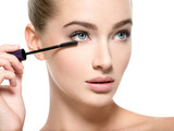 Girl makes makeup. Woman apply mascara on eyelashes - 220597291