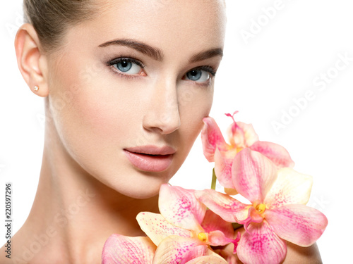 Beautiful young woman with flower in hand near at face. - 220597296