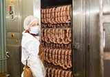 Female controlling hot processing of sausages - 220609899