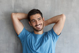 Portrait of handsome smiling young man in blue t-shirt leaning against gray textured wall with hands behind head - 220610012
