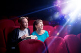 Romantic couple cuddling and watching the miraculous part of the film - 220610250