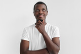 Daylight portrait of young african american man with dreamy cheerful expression, thinking, isolated on gray background - 220610653
