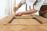 carpenter work the wood, measuring a thickness with angle square on wooden vintage door - 220613278