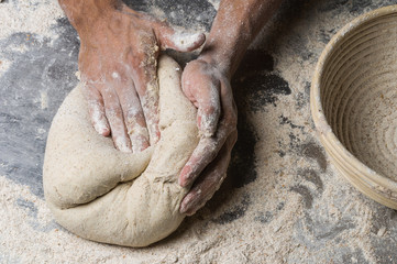 Male hands kneading dough on sprinkled
