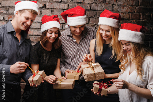 Leinwandbild Motiv Christmas party, New Year celebration, sale, black friday, holiday, fun, togetherness. Group of happy smiling people in Santa caps opening gift boxes