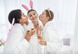 We love you. Beautiful young women in bathrobes having fun at spa salon. They holding glasses of champagne