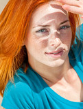 Beautiful red-haired woman blocking sun with her hand - 220624269