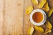 Leinwandbild Motiv Autumn tea on wooden table with leaves
