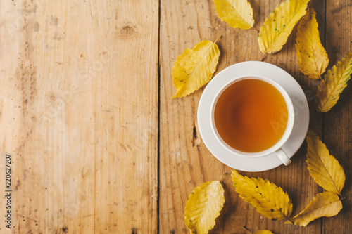 Fototapeta Autumn tea on wooden table with leaves