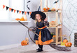 Leinwanddruck Bild - Happy Halloween. A little beautiful girl in a witch costume celebrates a home in an interior