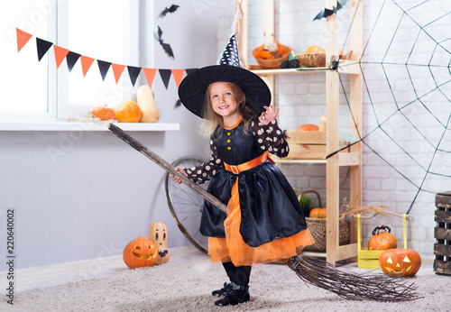 Leinwanddruck Bild Happy Halloween. A little beautiful girl in a witch costume celebrates a home in an interior