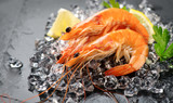 Shrimps. Fresh prawns on a black background. Seafood on crashed ice with herbs. Healthy food, cooking - 220643489