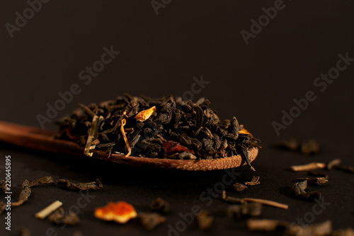 Tea leaves on a wooden spoon. Macro. Tea leaves on a black background. Isolate. Spoon with tea leaves close-up. - 220645895