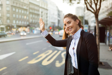 Business women waving for taxi