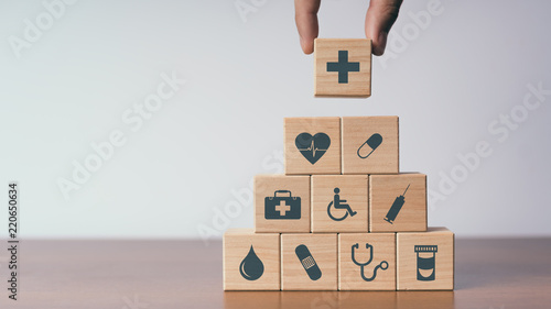 Foto Murales Concept of Insurance for your health, Hand hold wooden block with icon healthcare medical