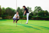Young couple playing golf - 220653074