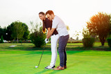 Male instructor showing woman to play golf - 220653096