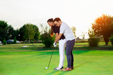 Male instructor showing woman to play golf - 220653487