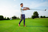 Man playing golf on a golf course in the sun - 220654283