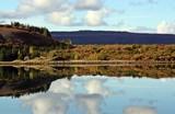 Fotografía de paisaje simétrico perfecto, bosque y lago con su reflejo y el del cielo nublado. Un paisaje de calma y tranquilidad en Islandia. - 220661222