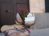 Scooter delivery with pink flowers in basket in front of door